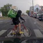 Rowerzysta-rozwoziciel na czerwonym przez pasy