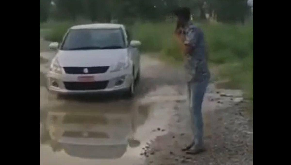 Pieszy obok auta wjeżdżającego w kałużę